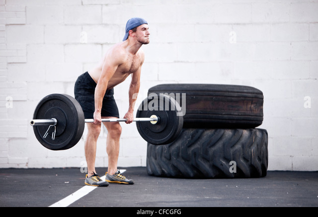 A young man clings weights while doing a fitness boot camp exercise. - Stock Image