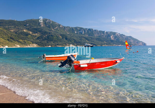 Agios Georgios, Corfu, Ionian Islands, Greece. Colourful boats moored in clear turquoise water, Cape Taxiarhis beyond. - Stock Image