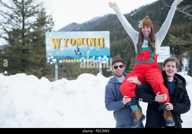 Men carrying woman on shoulder, Jackson Hole, Wyoming - Stock Image