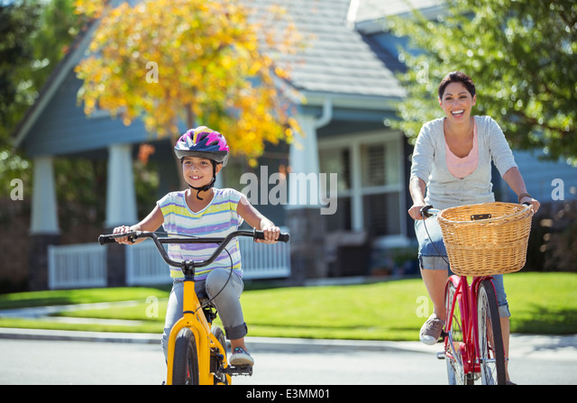 Mother and daughter riding bicycles in sunny street - Stock Image