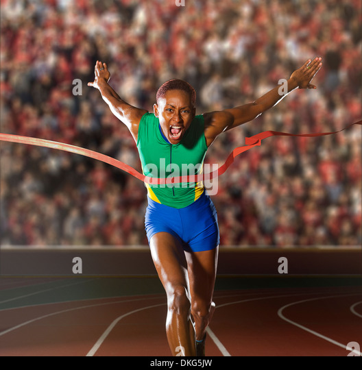 Young woman sprinting through winners tape in stadium - Stock Image