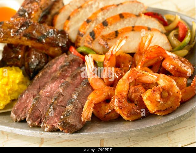 Shrimp, steak, chicken and pork rib fajitas over vegetables - Stock Image