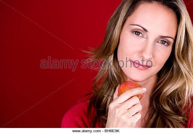 A mid adult woman holding a plum - Stock-Bilder
