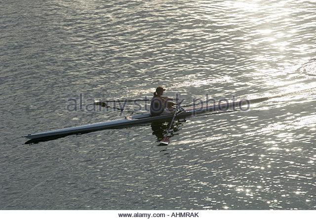 Woman rowing rowboat - Stock Image