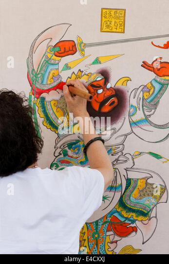 Woman painting Chinese warrior woodblock print - Stock Image