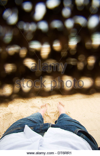 First Person Perspective Of A Man With A Straw Hat Covering His Eyes Lying Asleep At A Beachside Location - Stock Image