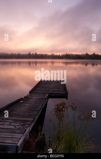 Lake Cassidy sunrise in fog and shoreline and dock - Stock Image
