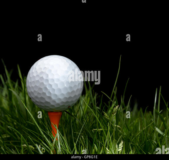 Golf Ball in long grass on a tee - Stock Image