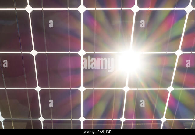Solar panels wit sun burst flare. Solar panel seen from behind, underneath. Solar cells on clear glass with sun - Stock Image
