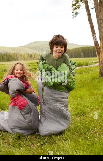 Boy and girl sack racing in sleeping bags - Stock-Bilder