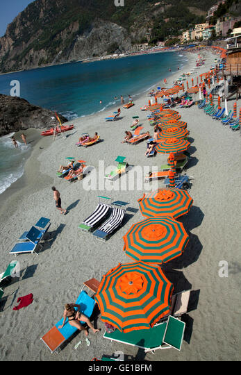 Orange and green striped beach umbrellas line the beach in Monterosso in the Cinque Terre, Italy. - Stock Image