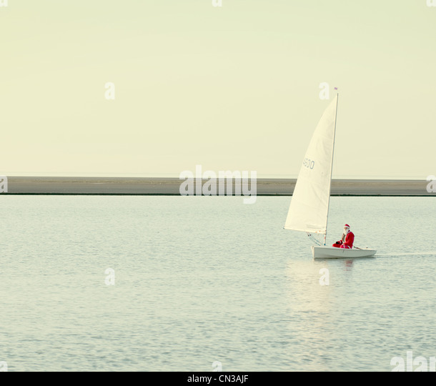 Person dressed up as santa claus in boat on lake - Stock Image