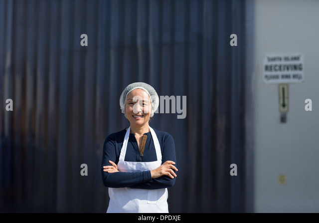Portrait of female factory worker, arms folded - Stock Image