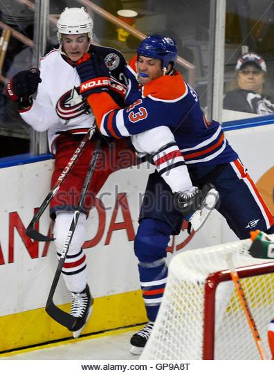 Columbus Blue Jackets' Nikita Filatov (L) and Edmonton Oilers' Jason Strudwick collide along the boards - Stock Image