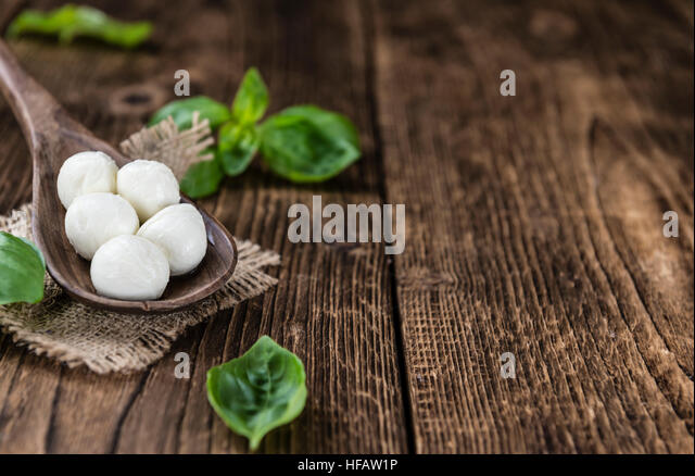 Small Mozzarella balls (on wooden background; selective focus) as close-up shot - Stock Image