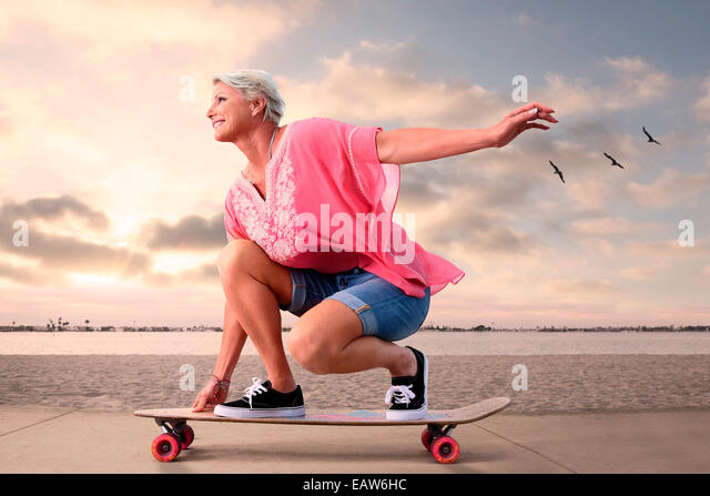 Youthful senior woman on skateboarding along beach at sunset, birds flying in the background. - Stock Image