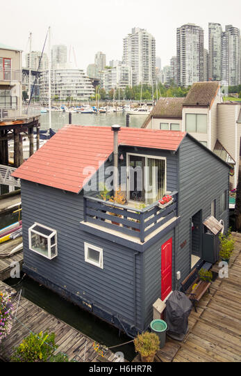 The Sea Village houseboats on Granville Island in Vancouver, Canada. The glass towers of Yaletown rise in the distance. - Stock Image