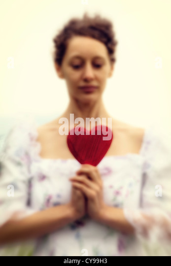 a woman in a period dress is holding a heart - Stock-Bilder