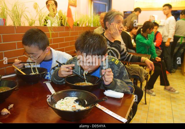 Shanghai China Huangpu District Sichuan Road restaurant inside interior Asian boy chopsticks eating noodles bowl - Stock Image