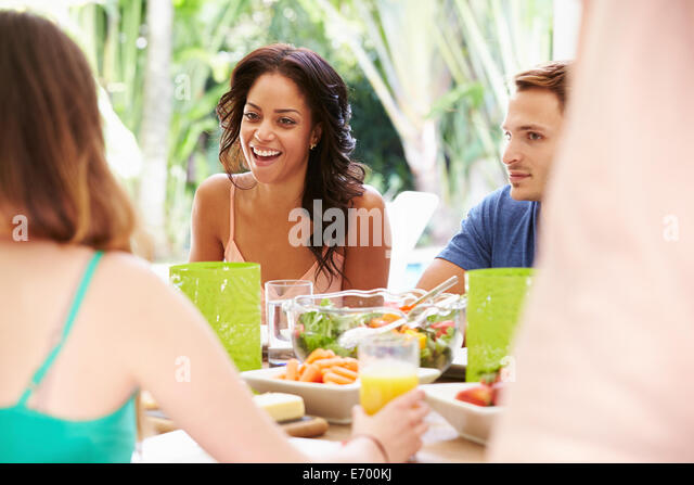 Group Of Friends Enjoying Meal Outdoors At Home - Stock Image