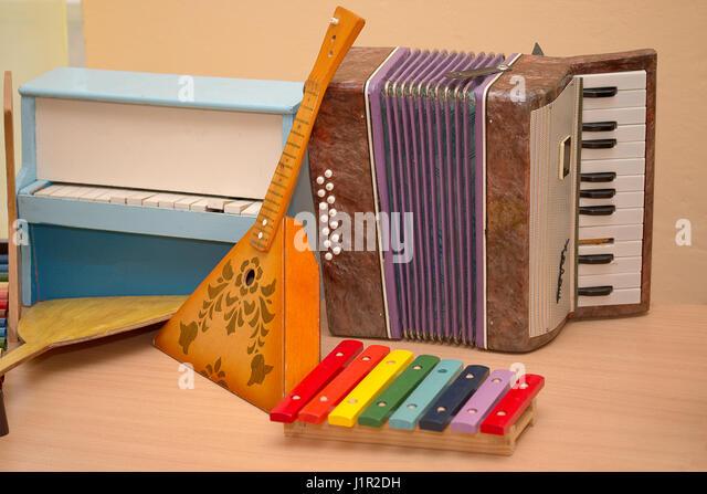 Antique antique toys musical instruments balalaika, accordion, harpsichord, piano - Stock Image