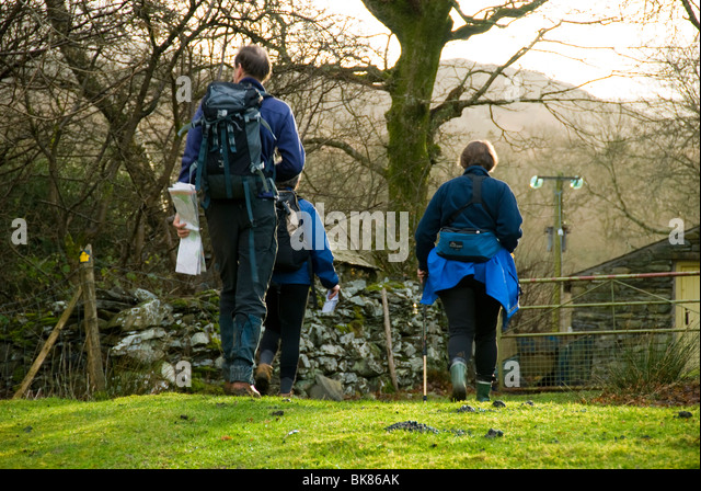 Three walkers going through a farm yard below Cadair Idris, near Dolgellau, Snowdonia, North Wales, UK - Stock Image