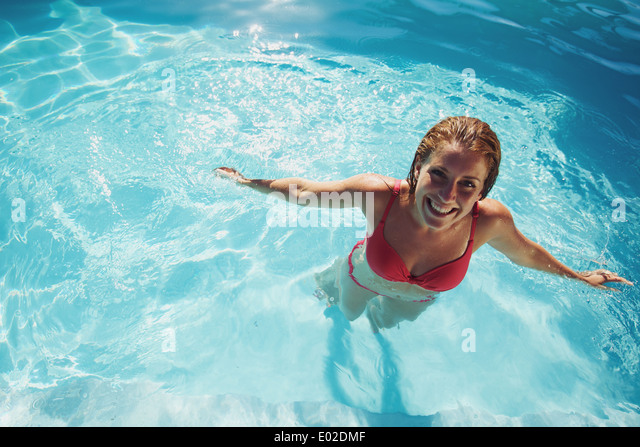 Happy young girl relaxing in a swimming pool. Smiling young woman wearing swimwear standing in pool looking at camera. - Stock Image