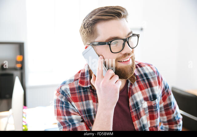 Happy attractive young man with beard in plaid shirt and glasses talking on cell phone in the office - Stock Image