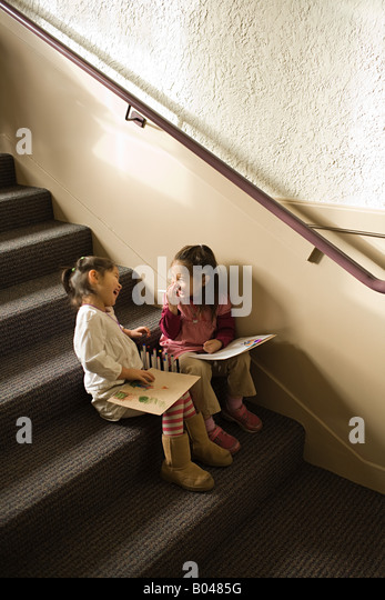 Girls sat on a step drawing and laughing - Stock Image