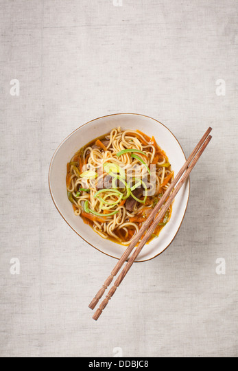 Asian noodles with pork and vegetables on textile background - Stock Image