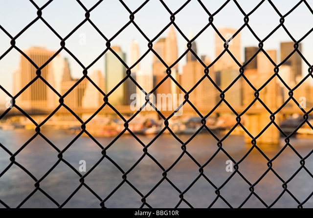 Skyscrapers behind a wire fence - Stock Image
