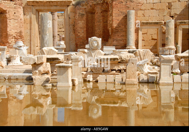 Head of a medusa and other wreckage mirror in water new forum Leptis Magna Libya - Stock Image
