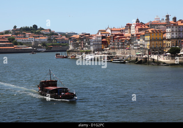 A boat cruises on the River Douro, past the Ribeira District, UNESCO World Heritage Site, Porto, Douro, Portugal, - Stock-Bilder