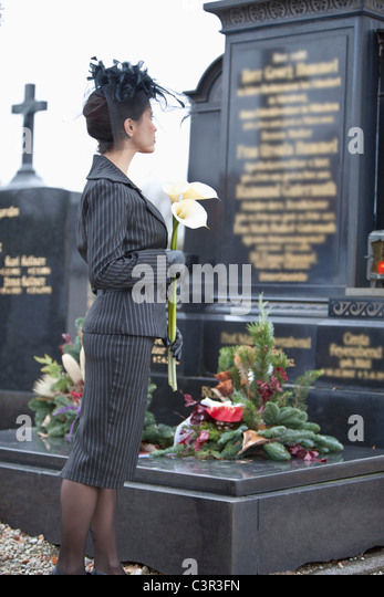 Germany, Bavaria, Young woman with flower at graveyard - Stock Image