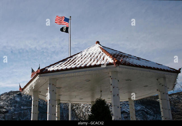 Snow covered gazebo with flags. - Stock Image