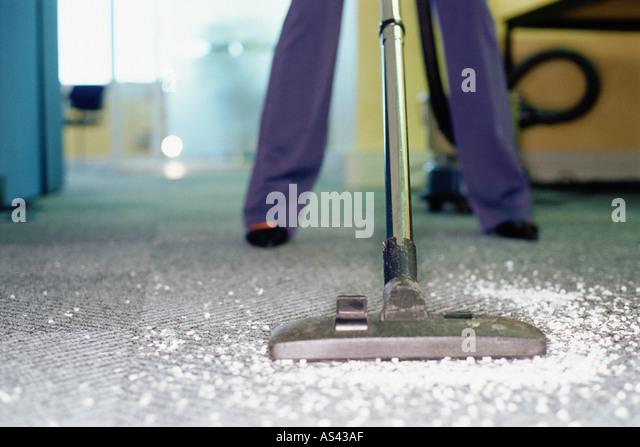 Woman vacuum cleaning a carpet - Stock-Bilder