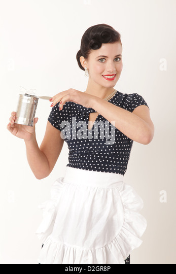 Woman wearing an apron holding can and tin opener - Stock Image