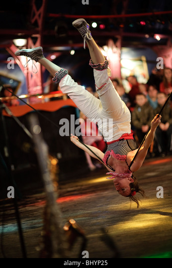 A young woman balancing upside down on the slack wire, No Fit State Circus, performing, Wales UK - Stock Image