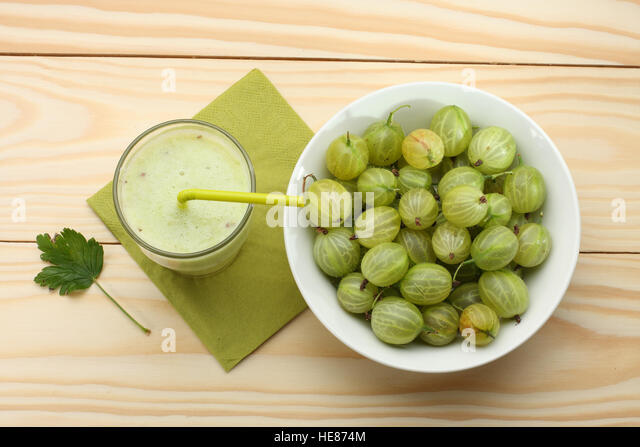 Smoothie from gooseberries in a glass and gooseberries in bowl  on wooden table - Stock Image