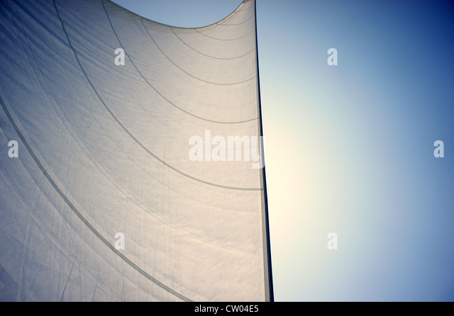Detail of  flared sails of a sailing yacht, making its way under the sun, across the Ionian Sea. - Stock Image
