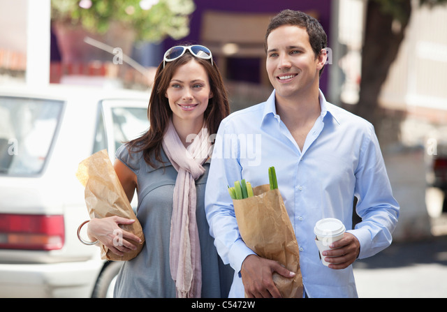 Smiling couple walking with paper bags full of vegetables - Stock Image