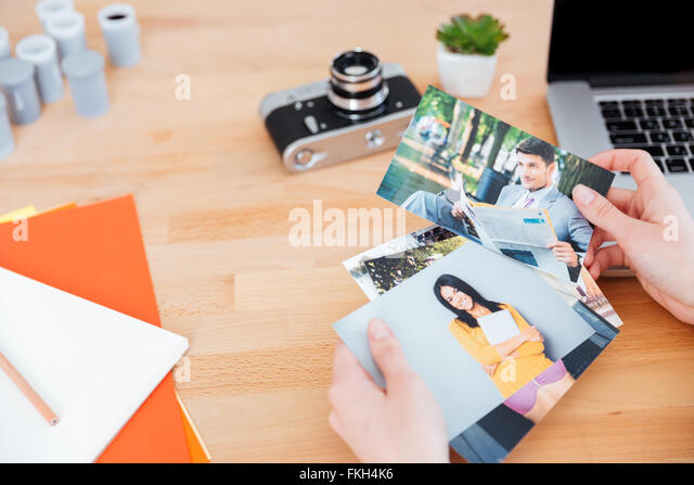Top view of photos of models holded by young woman photographer at the table - Stock Image