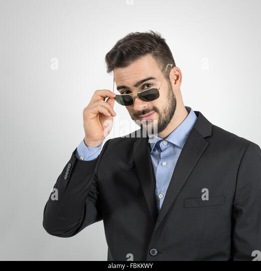 Young guy holding and looking over sunglasses. Desaturated portrait over gray studio background with retro vignette - Stock Image
