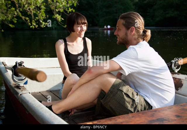 A young couple talking in a rowboat - Stock Image