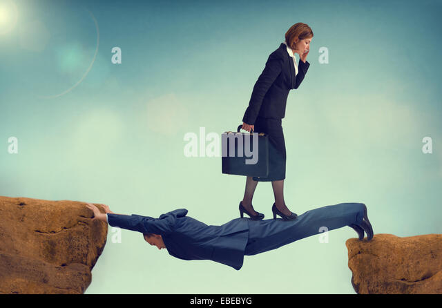 ruthless business woman walking over a vulnerable businessman - ambition concept - Stock-Bilder