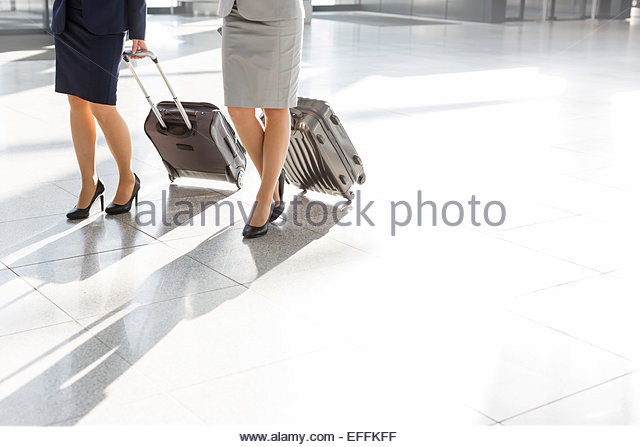 Low section of businesswomen walking at the airport - Stock Image