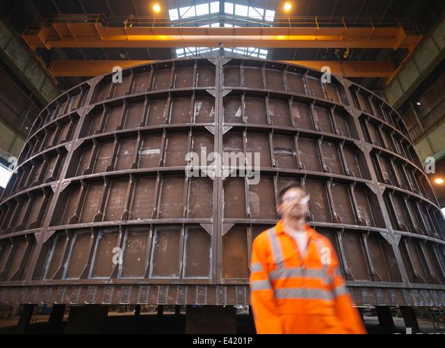 Engineer walking past marine fabrication - Stock-Bilder