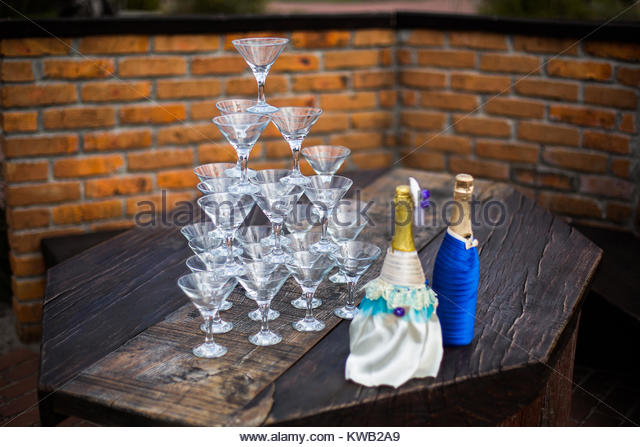 empty wine glasses are in the shape of a pyramid, decorated with bottles of champagne, wedding ceremony - Stock Image