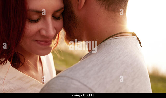 Close up shot of affectionate young woman embracing her boyfriend with her eyes closed. Romantic young couple together - Stock Image