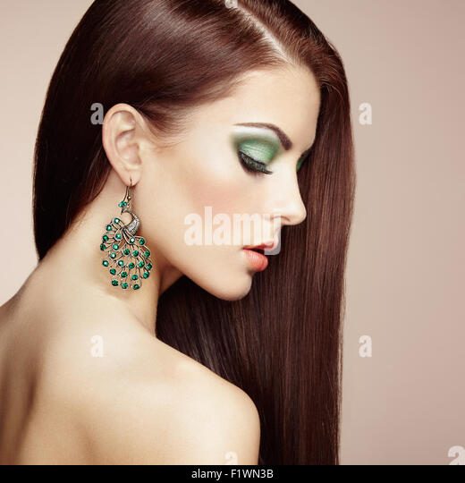 Portrait of beautiful brunette woman with earring. Perfect makeup. Fashion photo - Stock-Bilder